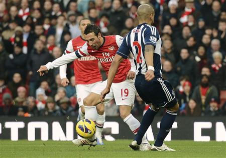 Arsenal's Cazorla challenges West Bromwich Albion's Reid during their English Premier League soccer match in London