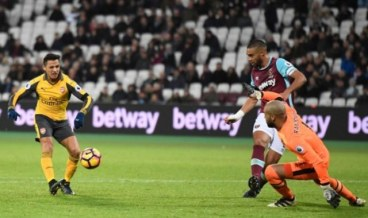Arsenal's Chilean striker Alexis Sanchez (L) scores his third goal, the team's fifth, during the English Premier League football match between West Ham United and Arsenal at The London Stadium, in east London on December 3, 2016. / AFP PHOTO / Justin TALLIS / RESTRICTED TO EDITORIAL USE. No use with unauthorized audio, video, data, fixture lists, club/league logos or 'live' services. Online in-match use limited to 75 images, no video emulation. No use in betting, games or single club/league/player publications. /